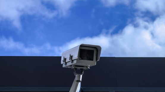 A cctv camera that has been installed on the outside of a office building